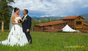 Bride and groom in a green grassy field with Rocky Mountains and a lodge in the background.